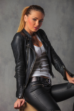 leather pants: rocker girl in black leather, side posing in studio background, seated and looking at the camera
