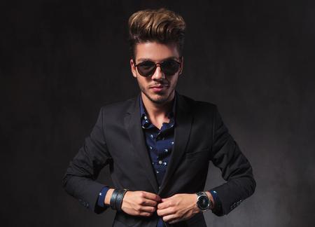 closing: elegant skinny model posing in dark studio background wearing sunglasses while closing his jacket