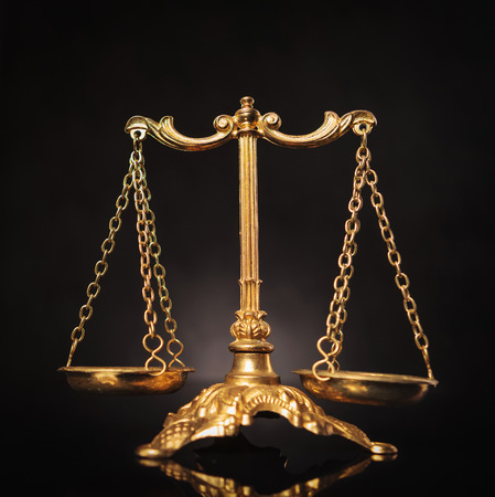 defendant: Symbol of justice, golden law scales on dark studio background Stock Photo