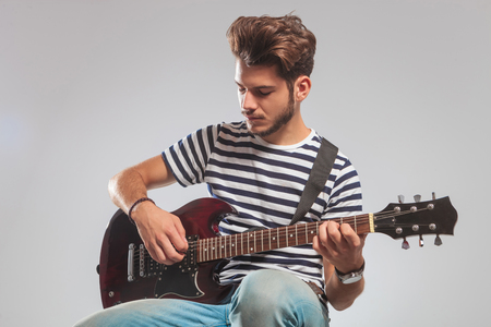 seated: guitarist pose seated in studio background while playing guitar with eyes closed Stock Photo