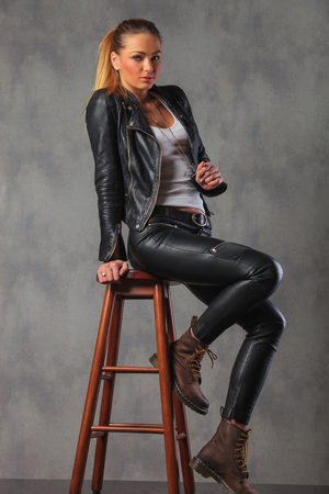 girl boots: hot blonde in leather jacket posing seated on stool in studio background looking at the camera