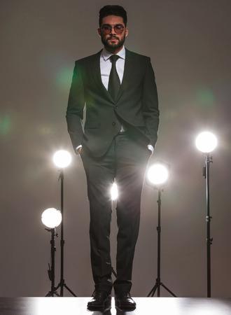 poses de modelos: apuesto hombre de negocios en traje negro de pie en el fondo del estudio con las manos en los bolsillos y focos de Foto de archivo