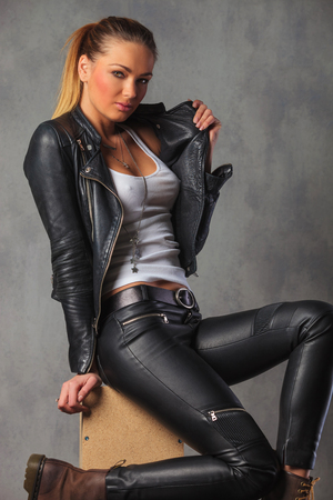 her: sexy rocker girl in leather posing seated on box in studio while fixing her jacket and looking at the camera