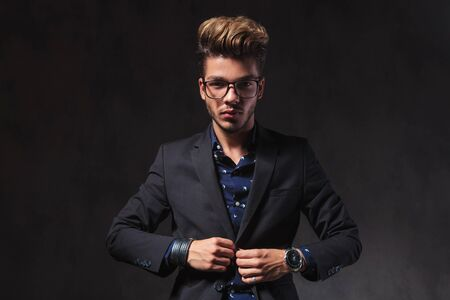 inteligent: portrait of fashionable smart man wearing glasses while looking at the camera in dark studio background
