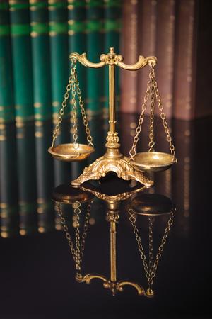justicia: Símbolo de la ley y la justicia, el derecho y la justicia concepto, escamas de oro delante de una fila de libros