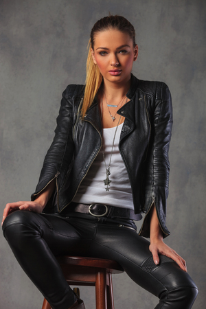 beautiful woman in leather jacket posing seated on stool in studio background looking at the camera