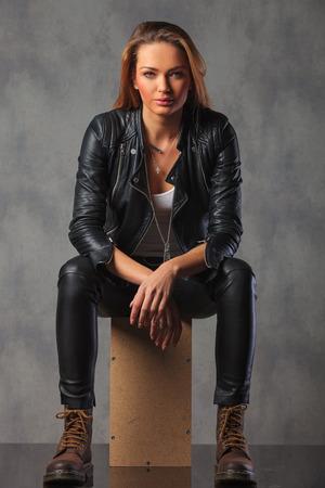 rocker girl: rocker en la chaqueta de cuero negro posando sentado en el fondo del estudio mirando a la cámara y descansando Foto de archivo