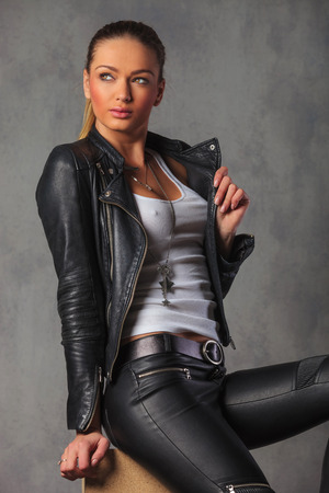 hot rocker girl posing seated in studio background while fixing her jacket and looking away from the camera Stock Photo