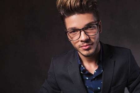 inteligent: portrait of fashionable smart man wearing glasses in dark studio background looking at the camera