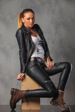 rocker girl in leather side posing seated in studio background while looking at the camera