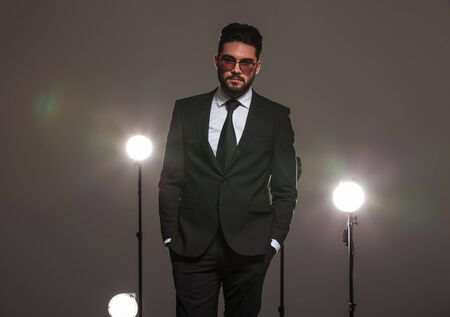 hombres negros: atractivo hombre de negocios en traje negro posando con las manos en los bolsillos en el estudio con focos
