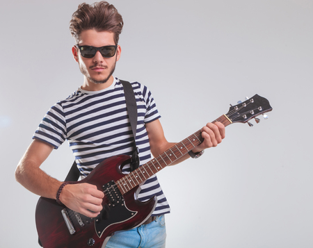 Portrait Of Rock Artist Posing In Studio Background While Leaning And Playing Electric Guitar Photo