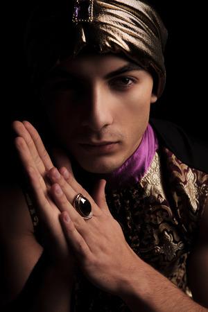 alladin: close portrait of man in golden alladin costume posing in dark studio background while touching palms
