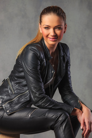 portrait of sexy girl in black leather posing seated, resting her hands on knees, while looking at the camera