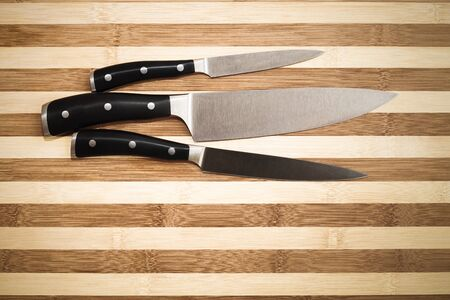 carvings: three kitchen knives over  bamboo  cutting board , 20 cm chefs knife, 16 cm carving knife and 12 cm utility knife