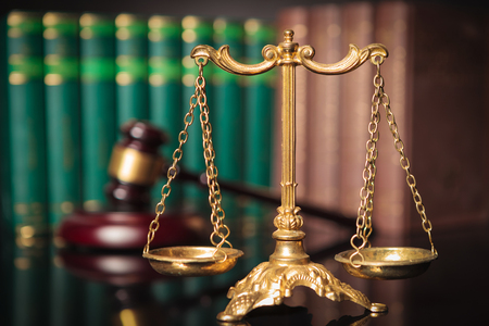 fair trial: golden scale in front of judges gavel and law books, justice concept
