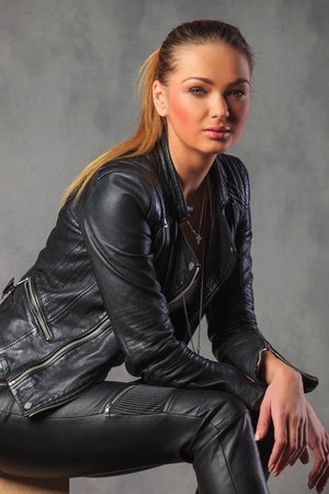 portrait of attractive blonde rocker seated in studio background, resting while looking at the camera Stock Photo