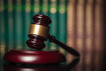 oracion: martillo de juez de madera delante de una fila de libros de derecho, la justicia concepto Foto de archivo