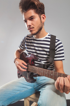 Young Guitarist Posing In Studio Background While Playing His Instrument Looking Away He Is Seated