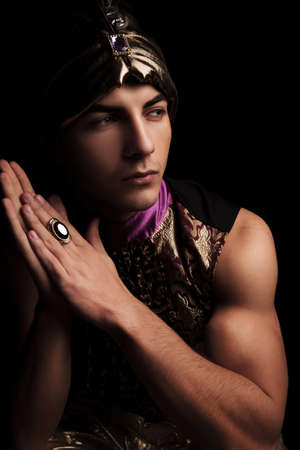 aladin: portrait of muscular man in masquerade costume posing in dark studio background while touching palms Stock Photo