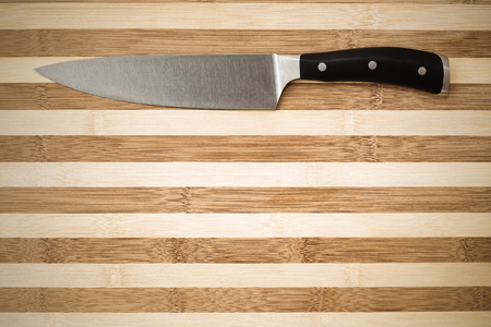 centimetres: 20 centimetres  chefs knife on a bamboo cutting board with plenty of copyspace under it Stock Photo