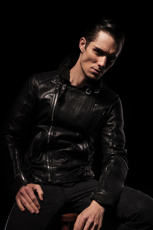 young man portrait: portrait of man in black leather rocker jacket posing seated in dark studio background looking at the camera Stock Photo