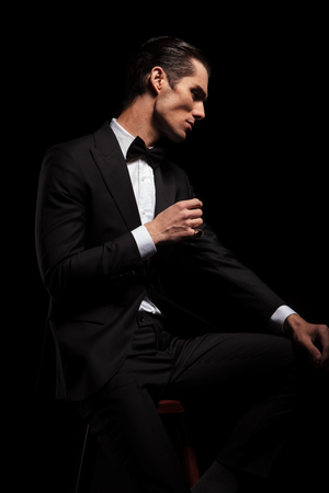 white suit: handsome skinny man in black suit with bowtie posing seated in dark studio background while resting his hands and looking away