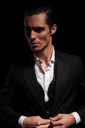 buttoning: portrait of young businessman in black suit posing in dark studio background closing his jacket and looking away