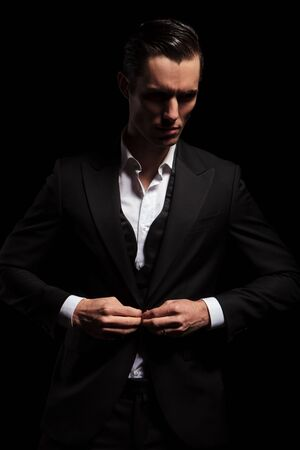 portrait of elegant man in black tuxedo posing in dark studio background while looking away and closing his jacket Stock Photo