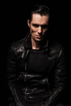 portrait of fashionable sexy biker in black leather jacket posing in dark studio background looking at the camera