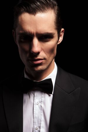 classy: close portrait of classy man in tuxedo with bowtie posing in dark studio background looking at the camera Stock Photo