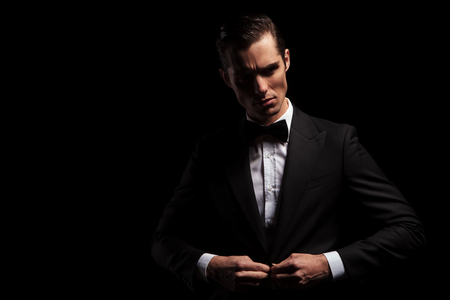 closing: portrait of confident handsome man in black suit with bowtie posing in dark studio background while closing his jacket