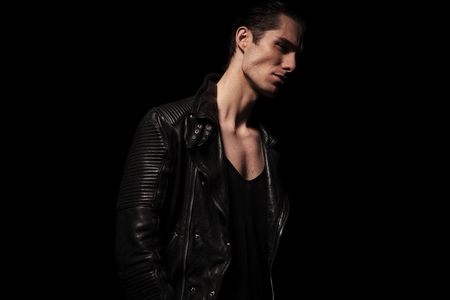 male hair: side portrait of sexy rocker in black leather jacket posing in dark studio background while looking away