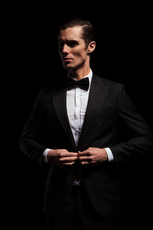 classy: side portrait of elegant businessman in black suit posing in dark studio background looking away and closing his jacket Stock Photo