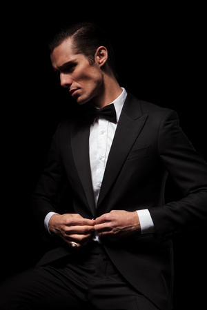 portrait of confident businessman in black suit with bowtie posing seated in dark studio background while closing his jacket and looking away Фото со стока
