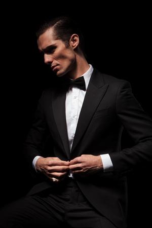 Retrato de hombre de negocios confía en traje negro con pajarita posando sentada en el estudio de fondo oscuro, mientras que el cierre de su chaqueta y mirando lejos Foto de archivo - 51930229