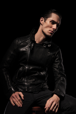 black male: young fashionable rocker in leather jacket posing seated in dark studio background looking away Stock Photo