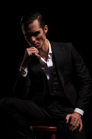hombre pensando: hombre de traje negro sentado en el estudio de fondo oscuro, mientras pensando y mirando hacia abajo