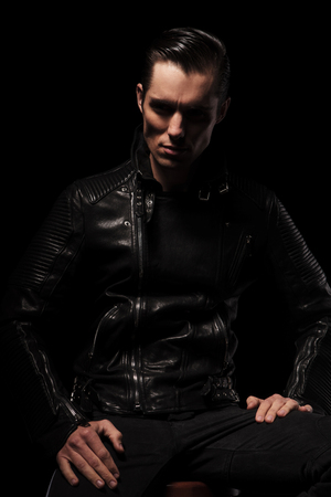 attractive male: attractive man in black leather jacket posing seated in dark studio background