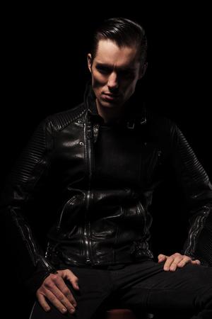 modelos hombres: hombre atractivo en chaqueta de cuero negro posando sentada en el estudio de fondo oscuro