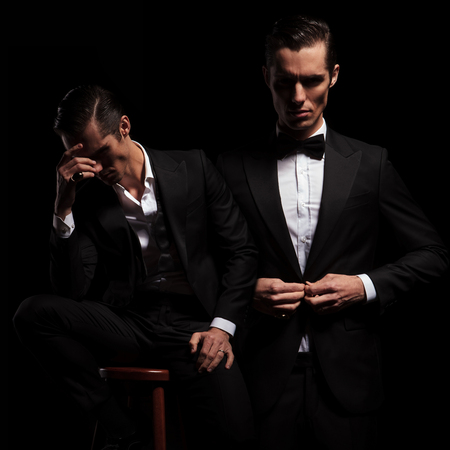 hair man: 2 poses of elegant businessman in black suit with bowtie. one seated thoughtful insecure and one confident closing his jacket. Stock Photo