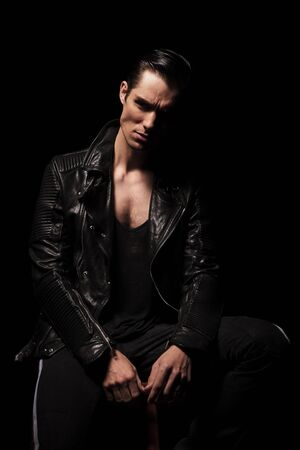 black male: fashionable rocker in black leather jacket posing seated in dark studio background while resting