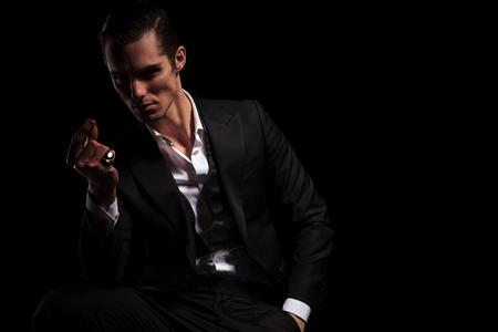 snaps: handsome model in tuxedo with hand in pocket snaps his fingers in dark studio background Stock Photo