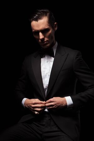 buttoning: portrait of classy businessman in black suit with bowtie posing seated in dark studio background while closing his jacket and looking down Stock Photo