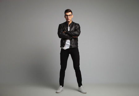 attractive man in black leather jacket wearing glasses posing in studio background with hands crossed