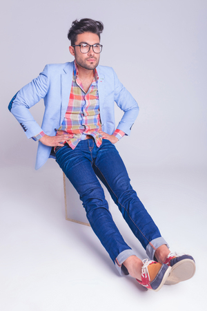 hands on waist: casual man wearing glasses and jeans seated on chair with hands on waist, while posing looking away and resting his legs