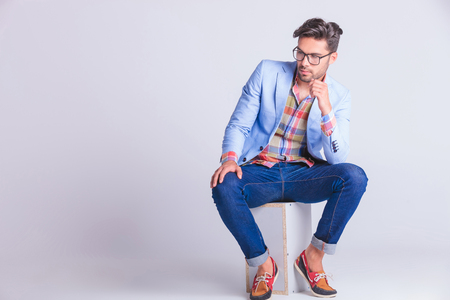 stylish men: smart casual man seated on box, wearing glasses and jeans, posing while looking away in studio background