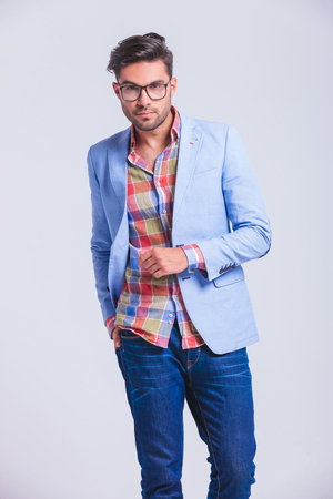 smart casual young man walking in studio background with hand in back pocket while looking at the camera