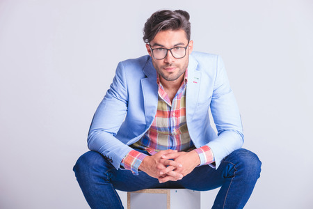 spread legs: close portrait of attractive businessman seated with legs spread open, touching hands, while wearing glasses and looking at the camera in studio background Stock Photo