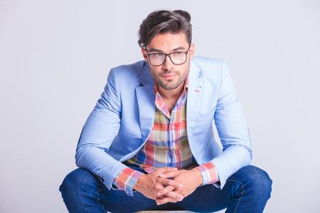 piernas hombre: cerrar el retrato de hombre casual atractiva, llevando gafas mientras posaba sentado con las piernas abiertas, mirando a otro lado en el fondo del estudio